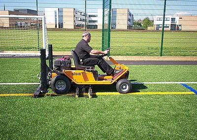 Andy Walker, Field Support Manager for Dennis and SISIS, demonstrates the SISIS Brush-Pro at one of the synthetic sports pitches that White Horse Cont